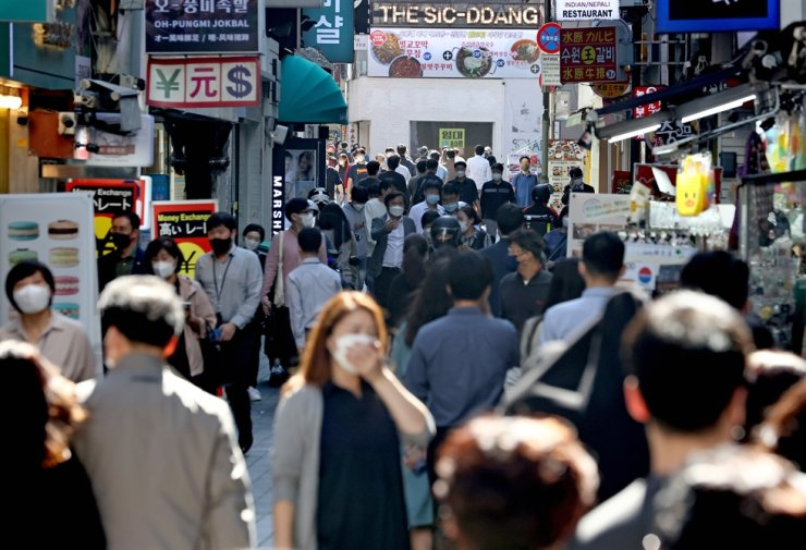 People walk through Myeong-dong in downtown Seoul, Wednesday. A government-civilian committee started discussing new quarantine and social distancing measures for a transition toward a