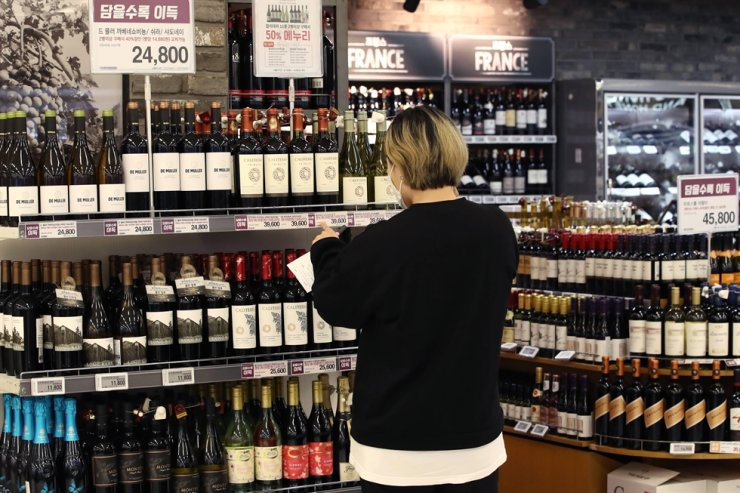 In this April 21 file photo, a shopper picks wine at a wine store. Yonhap
