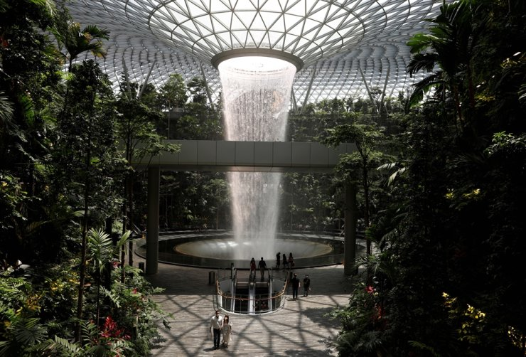 People walk past an indoor waterfall at Jewel Changi Airport in Singapore, Oct. 7. Korea and Singapore agreed Friday to exempt or ease vaccinated travelers from mandatory quarantine upon arrival, in a step to help revitalize people-to-people exchanges between the two sides in the midst of the prolonged COVID-19 pandemic. Reuters-Yonhap