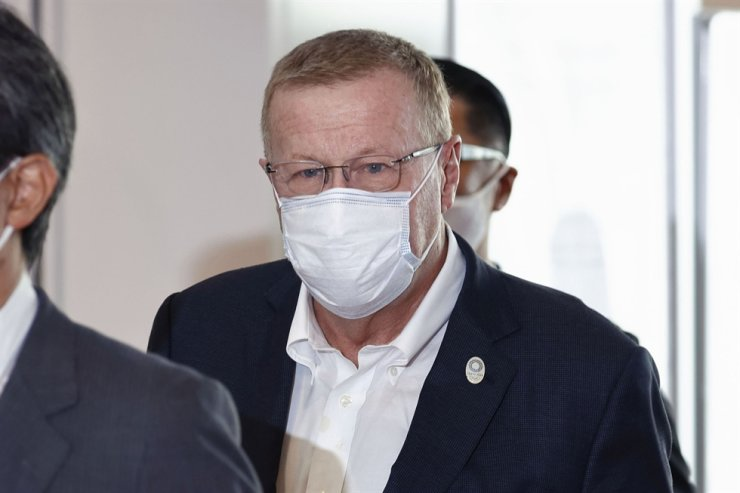 International Olympic Committee Vice President John Coates, center, wearing a face mask, arrives at Haneda Airport in Tokyo, June 15. AP-Yonhap