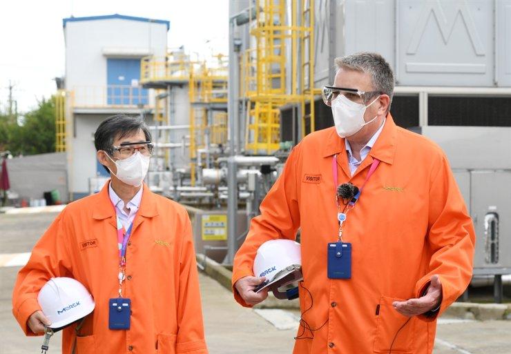 Kai Beckmann, CEO of Merck Electronics, and Wookyu Kim, managing director of Merck Korea, inspect the company's facility in Sihwa, Gyeonggi Province, Oct. 7. Courtesy of Merck Korea