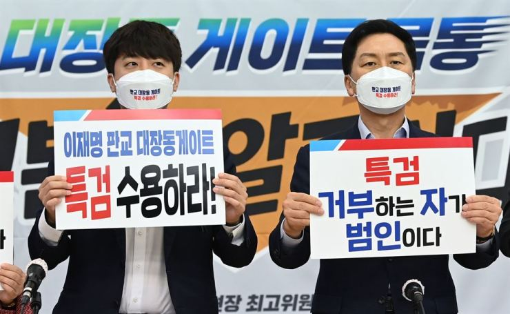 Main opposition People Power Party (PPP) leader Lee Jun-seok, left, and floor leader Rep. Kim Gi-hyeon hold placards at a party meeting in Suwon, Gyeonggi Province, Thursday, demanding the ruling Democratic Party of Korea (DPK) accept a special counsel investigation into a controversial land development project involving DPK presidential candidate Lee Jae-myung. Joint Press Corps