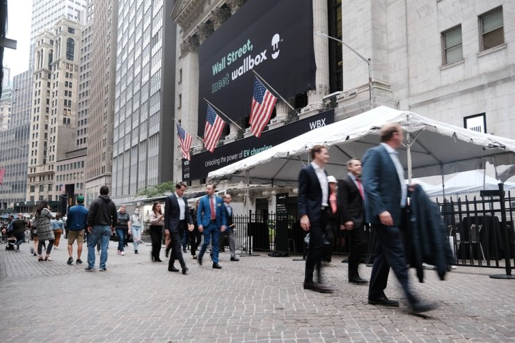 People walk outside of the New York Stock Exchange (NYSE), as global supply chain disruptions continue to affect the American economy, Oct. 4, in New York City. AFP-Yonhap