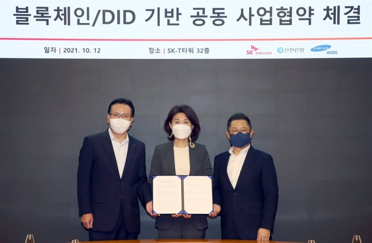 Shinhan Bank's digital group chief Jun Pil-hwan, left, poses with executives from SK Telecom and Samsung SDS after signing a partnership to jointly develop a blockchain-powered certificate service offering strengthened user security, at the telecom company's headquarters in Seoul, Tuesday. Courtesy of Shinhan Bank