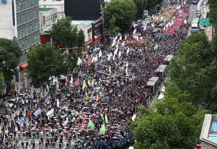 In this July 3 file photo, members of the Korean Confederation of Trade Unions (KCTU) hold a massive street rally in Seoul. Yonhap