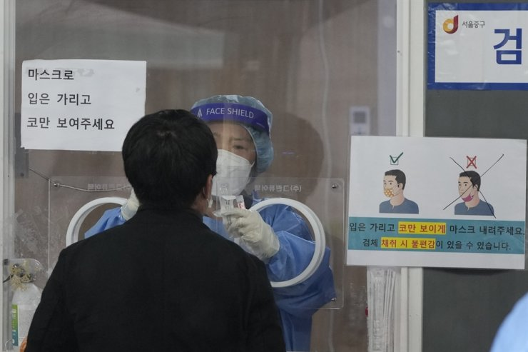 A medical worker wearing protective gear in a booth takes a sample from a person at a temporary coronavirus testing clinic in Seoul, Sept. 29, AP-Yonhap