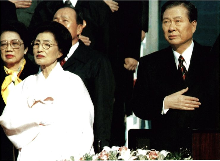 In this Feb. 25, 1998, file photo, President Kim Dae-jung, right, puts his hand on his heart during his inauguration ceremony. Kim tried to reform Korea's overseas adoption system. Despite policy changes, however, the reality remained much the same. Korea Times file