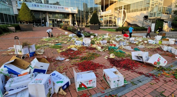 Vegetables lie scattered in front of Mapo District Office in Seoul, Oct. 9, thrown away by merchants at Mapo Agricultural and Marine Products Market in protest of the office's order to shut down the market after over 90 COVID-19 cases were found to be linked to it. Yonhap