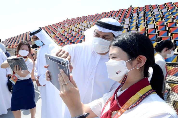 Volunteer workers at the Korea Pavilion demonstrate augmented reality (AR)-based experience using mobile devices to UAE officials on an external ramp overlooking the surrounding view of the Expo 2020 Dubai, Oct. 1. The pavilion is managed by state-run Korea Trade-Investment Promotion Agency (KOTRA). Courtesy of KOTRA