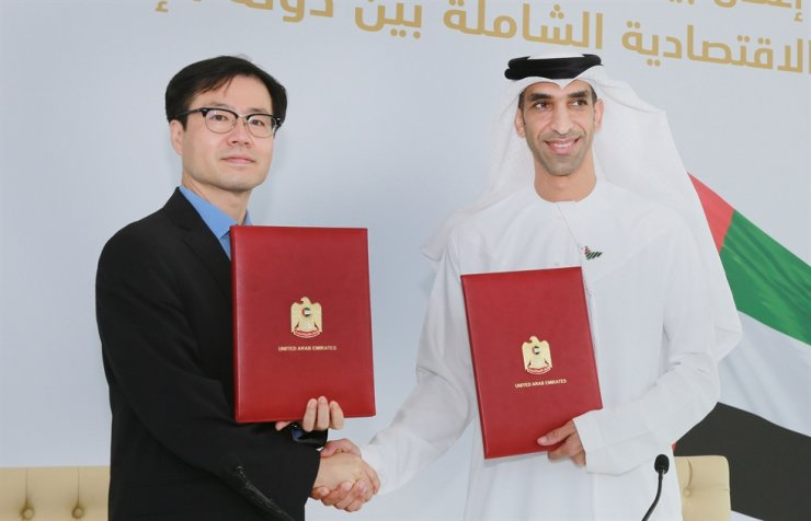 Trade Minister Yeo Han-koo, left, and United Arab Emirates Minister of State for Foreign Trade Thani Ahmed Al Zeyoudi shake hands after signing an agreement to push for a Comprehensive Economic Partnership Agreement in Dubai, Thursday (local time). Courtesy of the Ministry of Trade, Industry and Energy