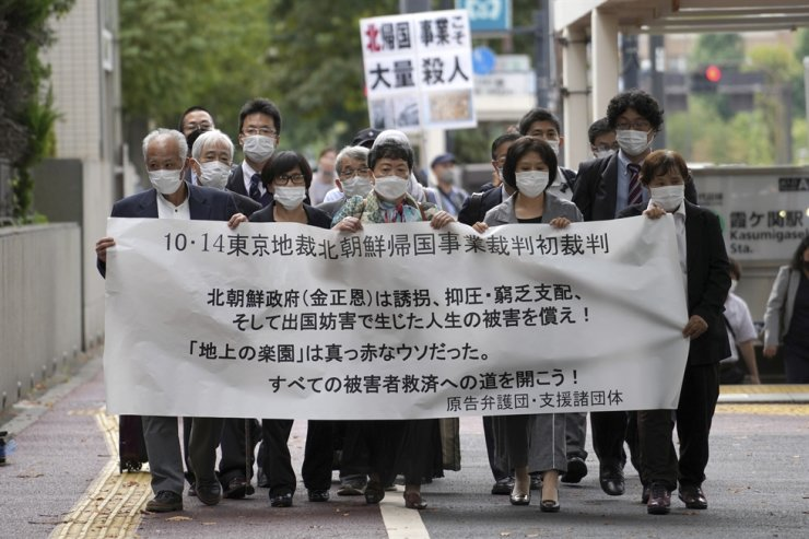 Plaintiffs and their supporters walk toward the Tokyo District Court in Tokyo, Oct. 14. The court is hearing five ethnic Korean residents of Japan and a Japanese national demanding the North Korean government pay compensation over their human rights abuses in that country after joining a resettlement program there that promised a