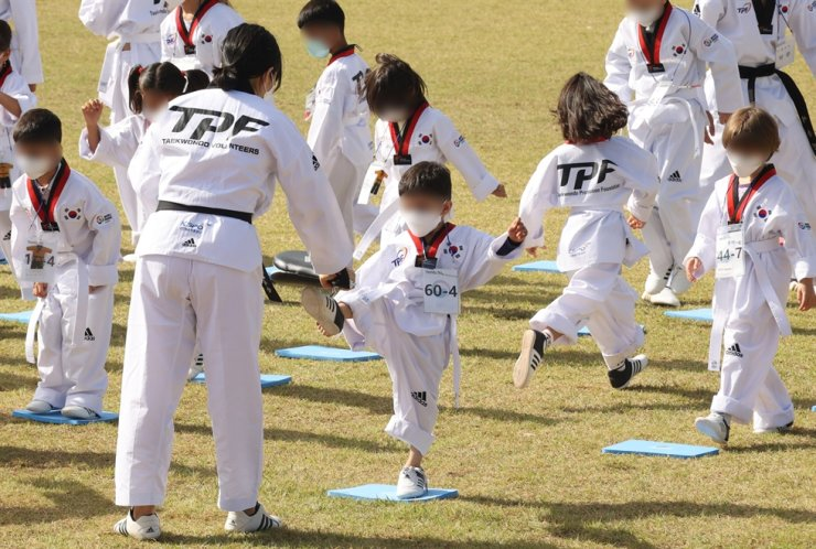 Afghan children attend a taekwondo class on a playing field at the Leadership Campus of the National Human Resources Development Institute in Jincheon, North Chungcheong Province, Wednesday. They arrived in Korea with their parents in late August when the Korean government evacuated Afghans who had worked with the Korean government after the Taliban took control of Afghanistan. Joint Press Corps