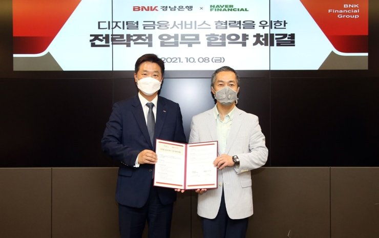 BNK Kyongnam Bank Managing Director Kim Jin-han, left, and Seo Rae-ho, Naver Financial's financial business department head, pose at the bank's main branch in Changwon, South Gyeongsang Province, Oct. 8, after signing a memorandum of understanding for strategic cooperation in digitizal financial services. Courtesy of BNK Kyongnam Bank