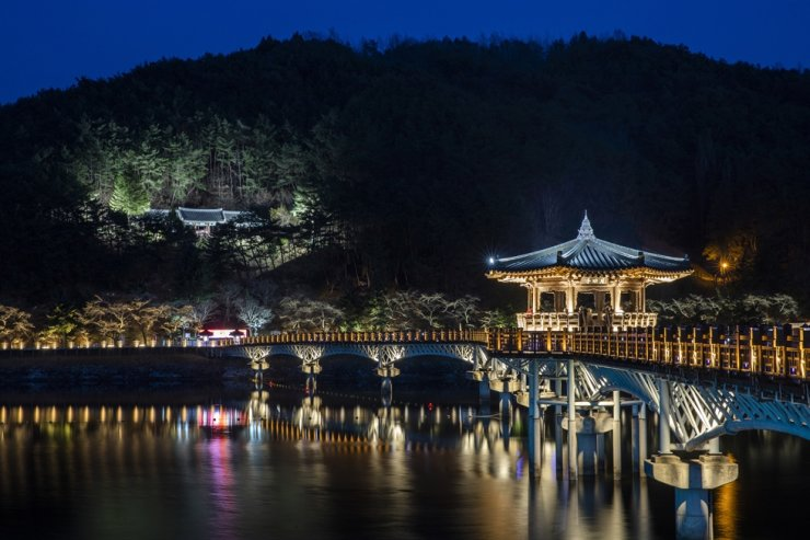 The reflection of Woryeong Bridge lit up at night is seen in the water of the Nakdong River in Andong, North Gyeongsang Province. Courtesy of Korea Tourism Organization