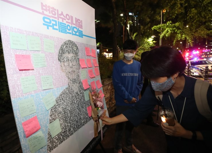 Citizens mourn in front of a photo wall of the late former staff sergeant Byun Hee-soo, who was forcibly discharged from the Army after receiving a gender-reassignment operation, in front of the Ministry of National Defense in Seoul, Thursday, after a local court ruled the discharge should be cancelled. Yonhap