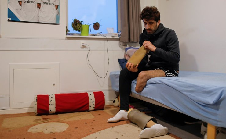 <span>Hoshang Rostami, 24, a Kurdish Iranian who lost part of his leg when stepping on a land mine aged 16 in Iran, prepares to attach a prosthetic limb in his bedroom at Kaershovedgaard, which was a former prison and is now a departure centre for rejected asylum seekers, in Jutland, Denmark, March 25, 2019. Reuters</span><br /><br />