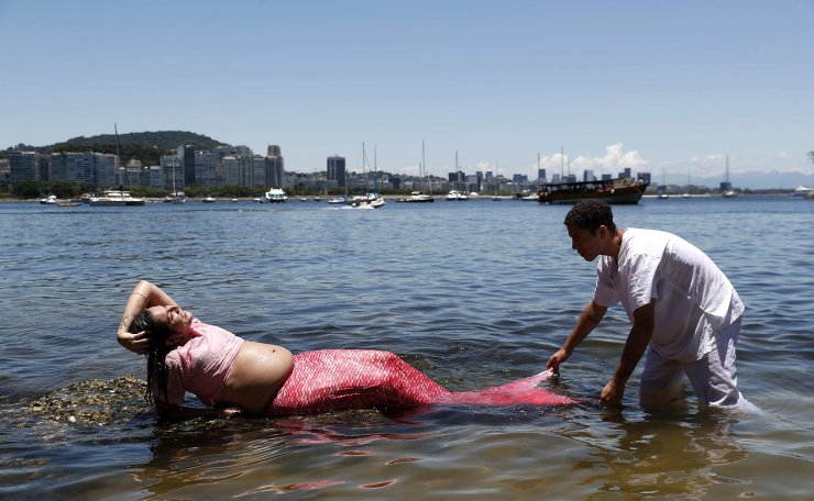 A medium of the Umbanda, one of the most recognized Afro-Brazilian religions, takes part in a ritual on the new year's eve incorporated in the spirit of 'Mariazinha da Praia' and disguised as a mermaid on the beach of Urca, Rio de Janeiro, Brazil, 31 December 2019. EPA