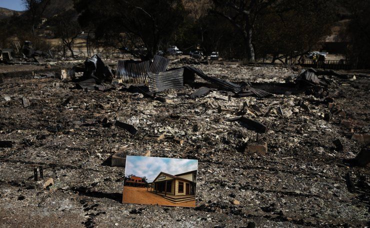 A before photo is placed on the remains of a building leveled in the Woolsey Fire at decimated Paramount Ranch during U.S. Secretary of the Interior Ryan Zinke's visit to the ranch Thursday, Nov. 15, 2018, in Agoura Hills, Calif. AP