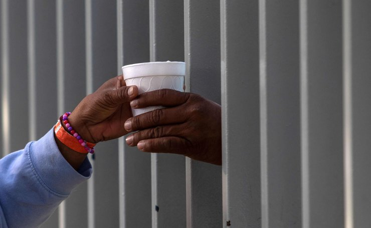 A migrant travelling with other Central American migrants -mostly Hondurans- moving towards the United States in hopes of a better life, buys a cup of hot chocolate through the fence of a shelter in Tijuana, Mexico, on November 19, 2018. AFP