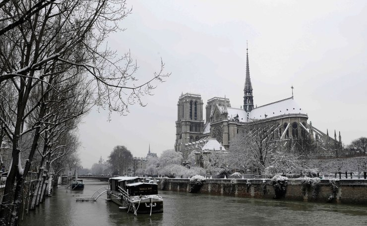 This file photo taken on February 7, 2018 shows snow covered houseboats on the Seine river near the Notre-Dame de Paris cathedral following heavy snowfall in Paris. AFP