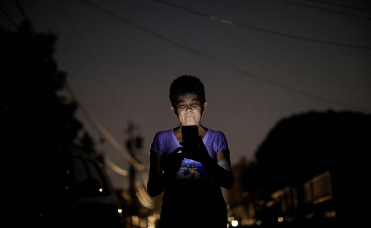 Maria Esis, 52, a kidney disease patient, uses a telephone in front of her house during a blackout in Maracaibo, Venezuela April 11, 2019. Reuters