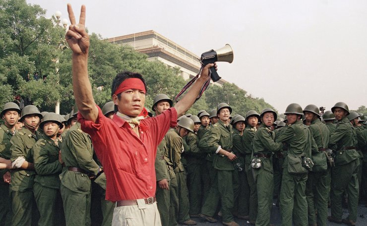 FILE - In this Saturday, June 3, 1989 file photo, a student pro-democracy protester flashes victory signs to the crowd as People's Liberation Army troops withdraw on the west side of the Great Hall of the People near Tiananmen Square in Beijing. AP