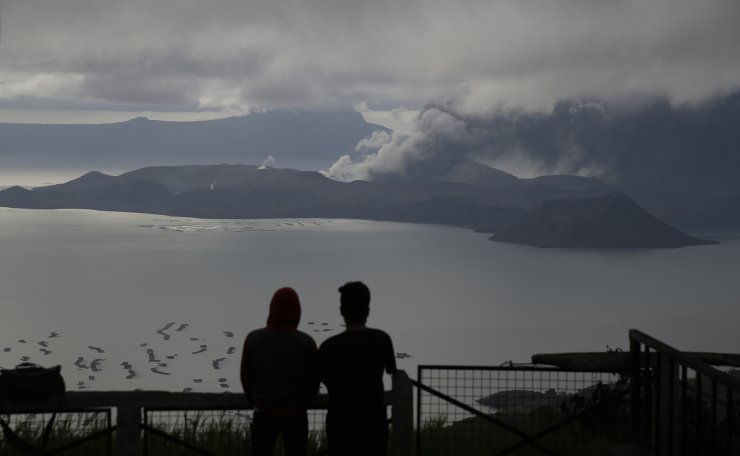 Men watch from Tagaytay, Cavite province, south of Manila, as Taal Volcano continues to spew ash on Tuesday, Jan. 14, 2020. Thousands of people fled the area through heavy ash as experts warned that the eruption could get worse and plans were being made to evacuate more. AP