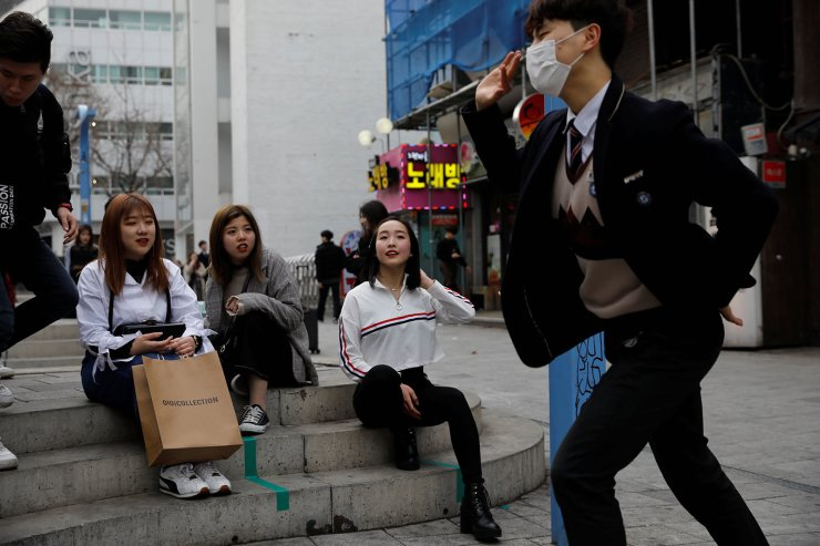Japanese Yuuka Hasumi, 17, who wants to become a K-pop star, watches her friend's performance during their street performance in Hongdae area of Seoul, South Korea, March 21, 2019. Reuters
