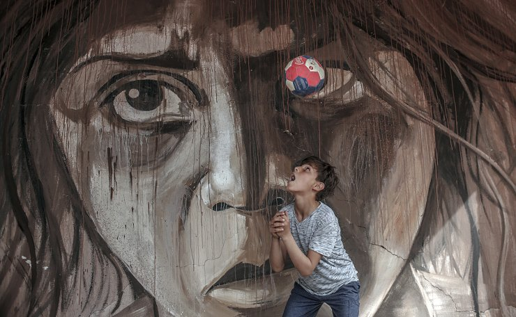 A boy plays with a ball in front of a mural painted by Palestinian artist Ali Al-Jbaly for his exhibition 'dreamers among the rubbles' between a rubble of a destroyed building damaged during the Israeli war against Gaza in summer 2014, in Gaza City, Gaza Strip, 30 April 2019. EPA