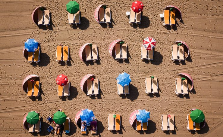 An aerial image of beach umbrellas and deck chairs as beachgoers enjoy the hot weather at a beach in Scheveningen, the Netherlands, 24 July 2019. The Royal Dutch Meteorological Institute has issued an official warning due to high temperatures affecting the country as well as Western Europe. EPA
