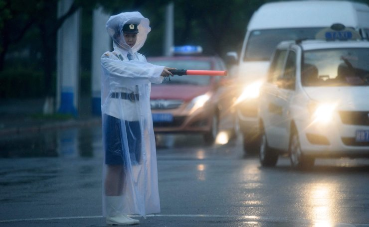 <span>A traffic warden conducts traffic during rainfall in Pyongyang on June 18, 2019. AFP</span><br /><br />