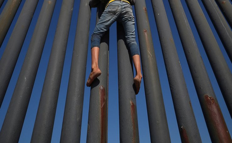 A migrant, part of a caravan of thousands from Central America trying to reach the United States, climbs the border fence between Mexico and the United States, in Tijuana, Mexico, November 18, 2018. Reuters