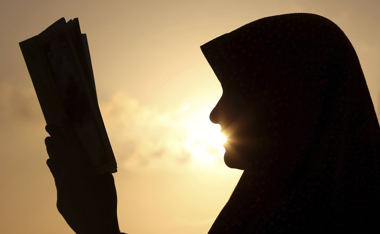In this July 4, 2014 file photo, a Palestinian girl reads the Quran, Islam's holy book during Ramadan, at sunset in Gaza City. Most Muslims around the world began fasting on Monday, May 6, 2019, for the start of the month of Ramadan. AP