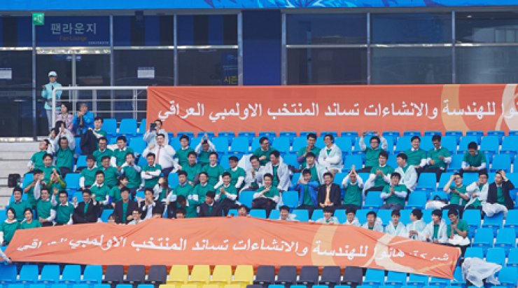 A group of employees from Hanwha Engineering & Construction cheer for the Iraqi national football team during its Oct. 2 match with Thailand at the Incheon Football Stadium. The Iraqis won 1-0 to capture the bronze medal at the Incheon Asian Games. / Courtesy of Hanwha Engineering & Construction