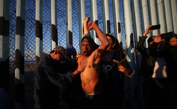 Paulino, a migrant man from Honduras, part of a caravan of thousands from Central America trying to reach the United States, gestures at the border fence between Mexico and the United States, in Tijuana, Mexico, November 18, 2018. Reuters