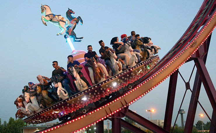 FILE - In this June 16, 2018 file photo, people take a ride at an amusement park during Eid al-Fitr celebrations, that mark the end of the Muslim holy fasting month of Ramadan, in Baghdad, Iraq. Most Muslims around the world began fasting Monday, May 6, 2019, to mark the start of Ramadan. The end of Ramadan is marked by intense worship, early morning Eid prayers the day after Ramadan and then families typically spend the day at parks, eating in the sunshine for the first time in a month. AP