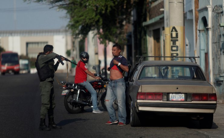 A Venezuelan police officer orders a man to lift his shirt, during a blackout in Maracaibo, Venezuela, April 12, 2019. Reuters