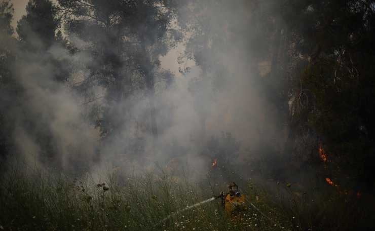 Fire fighters extinguish a forests fire near Kfar Uriya, Thursday, May 23, 2019. Israeli police have ordered the evacuation of several communities in southern and central Israel as wildfires rage amid a major heatwave. AP