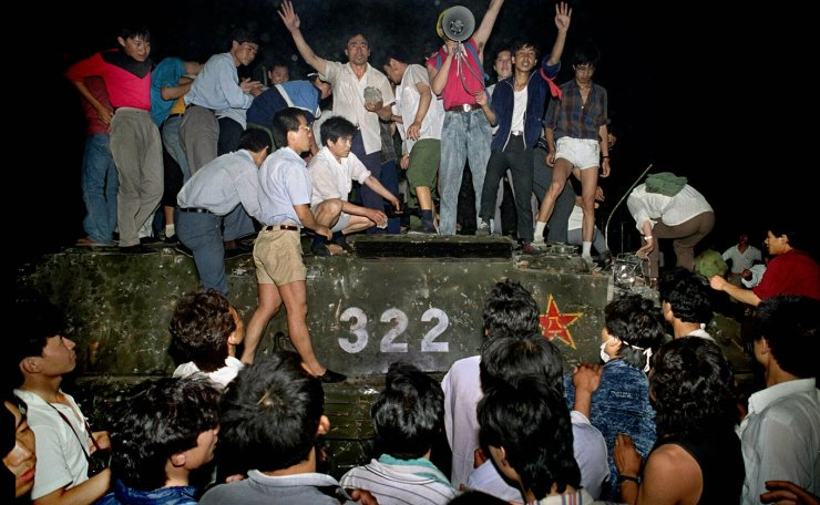 In this early June 4, 1989, file photo, civilians hold rocks as they stand on a government armored vehicle near Changan Boulevard in Beijing. AP