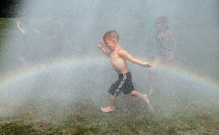 A child rinses himself off after participating in Mud Day at the Nankin Mills Park, Tuesday, July 9, 2019, in Westland, Mich. The annual day is for kids 12 years old and younger. While parents might be welcome, this isn't an event meant for teens or adults. It's all about the kids having some good, unclean fun during their summer break and is sponsored by the Wayne County Parks. AP