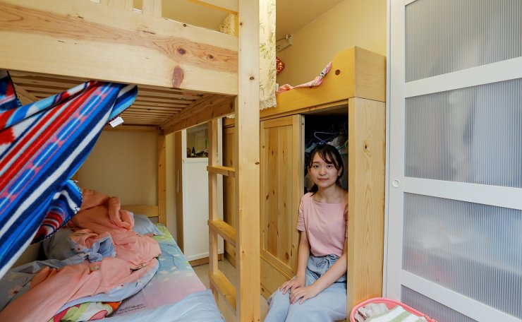 Native Hong Kong resident Ruka Tong, 21, a student, poses for a picture in her bedroom of her family's apartment in Hong Kong, China June 28, 2019. Tong shares her 11 sq meter room with two of her sisters. Their Parents live in the same apartment. Until last year, the family of five lived in a 28 sq meter room. 'You see me always at work to earn more money to buy a flat. I work seven days a week in five jobs. One office job and four jobs giving tutorial classes. Just 2-3 hours resting time. I need to earn more money to save for academia and for my family,' Tong said. 'There are so many pressures in Hong Kong, price pressure, academic pressure.. I don't want the future generation to face this problem.' Reuters