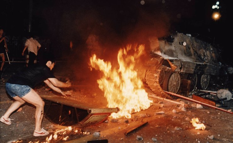 FILE - In this June 4, 1989 file photo, a student protester puts barricades in the path of an already burning armored personnel carrier that rammed through student lines during an army attack on anti-government demonstrators in Beijing's Tiananmen Square. AP