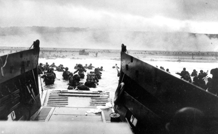 FILE - In this June 8, 1944, file photo, under heavy German machine gun fire, American infantrymen wade ashore off the ramp of a Coast Guard landing craft during the invasion of the French coast of Normandy in World War II. June 6, 2019, marks the 75th anniversary of D-Day, the assault that began the liberation of France and Europe from German occupation, leading to the end World War II. AP