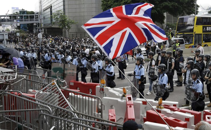 A man waves a British flag as policemen in anti-riot gear stand guard against the protesters on a closed-off road near the Legislative Council in Hong Kong, Wednesday, June 12, 2019. AP