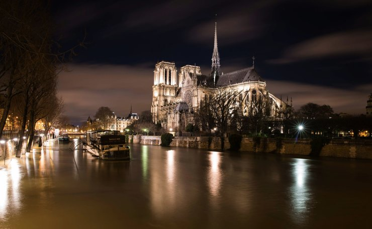 This file photo taken on the night of January 29, 2018 in Paris shows the flooded banks of the Seine river near the Notre-Dame de Paris Cathedral. AFP