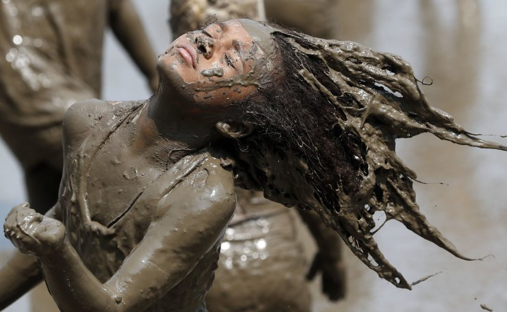 Jaylee Fogg, 10, throws back her mud crusted hair during Mud Day at the Nankin Mills Park, Tuesday, July 9, 2019, in Westland, Mich. The annual day is for kids 12 years old and younger. While parents might be welcome, this isn't an event meant for teens or adults. It's all about the kids having some good, unclean fun during their summer break and is sponsored by the Wayne County Parks. AP