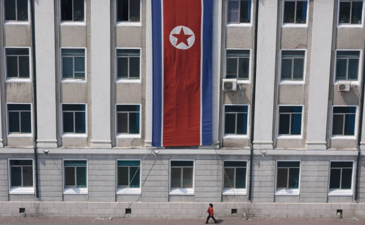 In a photo taken on April 12, 2019 a pedestrian walks past a North Korean flag displayed on a building in Pyongyang. AFP