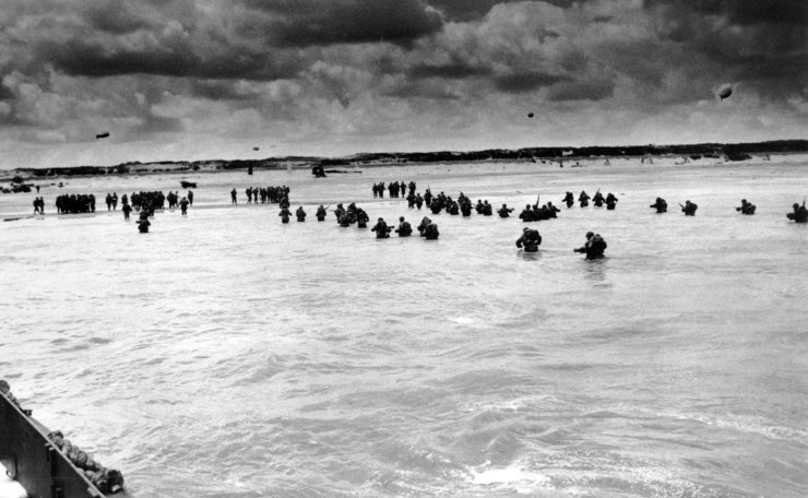 FILE - In this June 1944, file photo, U.S. reinforcements wade through the surf as they land at Normandy in the days following the Allies', D-Day invasion of occupied France. AP