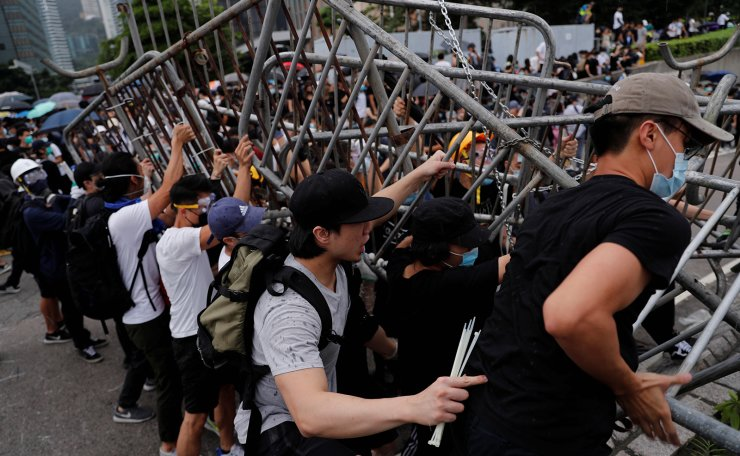 Demonstrators attempt to move metal barricades during a protest against a proposed extradition bill in Hong Kong in Hong Kong, China June 12, 2019. Reuters