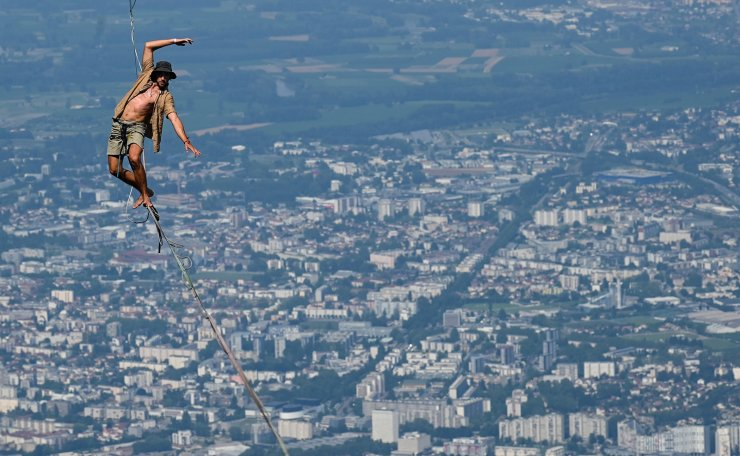 A man walks on a slackline during the 7th edition of the European 'Marmotte Highline Project' (MHP) festival in Lans-en-Vercors, near Grenoble, eastern France, on July 4, 2019. - The event, during which the participants will be able to evolve on the various highlines located in the Regional Natural Park of Vercors, takes place until July 7, 2019. AFP